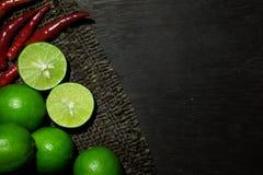 Limefrukter och chili på mörkt trä Arkivfoto