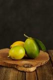 Limefrukter och citroner på träbräde Arkivbilder