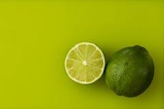 Limefrukter på en grön bakgrund Royaltyfria Foton