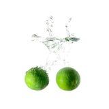 Limefrukter plaskar på vatten på vit bakgrund Royaltyfria Bilder