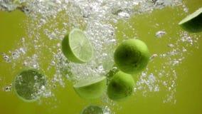 Limefrukter som faller in i vatten