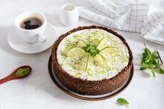 Limefruktostkaka med pepparmint Ostkaka med koppen kaffe på vit bakgrund Bästa sikt, kopieringsutrymme royaltyfri foto