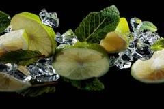Limefruktstycken med sidor av pepparmint på svart bakgrund Arkivbild