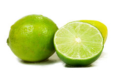 Limes. Fresh limes on white and sprayed with water drops Royalty Free Stock Photography
