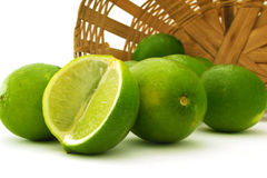 Limes. Some limes falling from a basket Stock Images