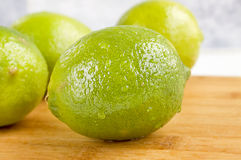 Limes. Fresh whole limes on a cutting board Stock Image
