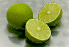 Limes. Green limes ruits on a silver tray Stock Images