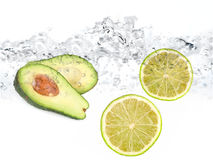 Limes and avocado in water Royalty Free Stock Photos