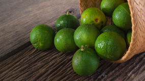 Limes. In bamboo basket on wooden board Royalty Free Stock Images