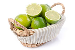 Limes in a basket. Isolated on white Stock Photos