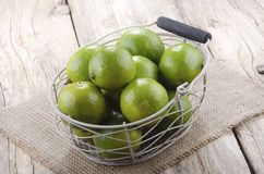Limes in a basket on a jute cloth Royalty Free Stock Photography