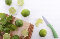 Limes on chopping board. Royalty Free Stock Images