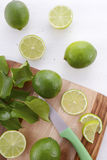 Limes on chopping board. Stock Photos
