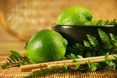 Limes with chopsticks Stock Photos