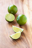 Limes on cutting board Stock Photos