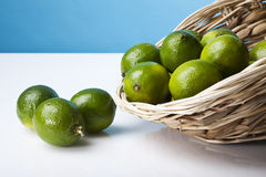 Limes falling from a basket Stock Photo