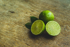 Limes. Fresh limes in a bowl with leaves cut in half on wooden table, Top view, background Royalty Free Stock Photo