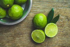 Limes. Fresh limes in a bowl with leaves cut in half on wooden table, Top view, background Royalty Free Stock Photos