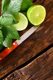 Limes and knife. On wooden board. Stock Image