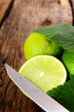 Limes and knife. On wooden board. Royalty Free Stock Photos