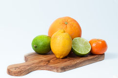 Limes, lemon, orange and tangerine on a wooden table, isolated on white Royalty Free Stock Photo