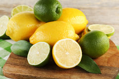 Limes and lemons. Ripe limes and lemons on cutting board with napkin Stock Photo