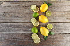 Limes and lemons. Ripe limes and lemons on wooden table Royalty Free Stock Images
