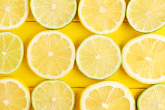 Limes and lemons. Slices of limes and lemons on yellow wooden table Stock Images