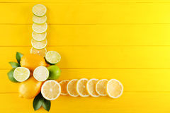 Limes and lemons. Slices of limes and lemons on yellow wooden table Stock Photos