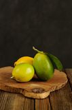 Limes and lemons on wooden board Stock Images