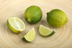 Limes and lime slices on a wooden cutting board Stock Photos