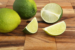 Limes and lime slices on a wooden pad Royalty Free Stock Image
