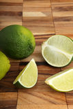 Limes and lime slices on a wooden pad Stock Photo