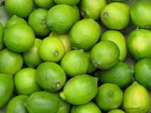 Limes Limes Limes. A green metal bowl filled with green limes Stock Photos