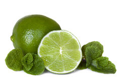 Limes and Mint. Limes, whole and cut, with mint leaves.   on white Stock Photo
