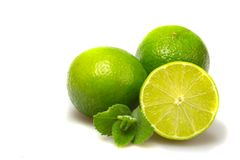 Limes with mint leaves on white. Royalty Free Stock Image
