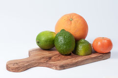 Limes, orange and tangerine on a wooden table, isolated Stock Photo