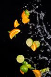 Limes and oranges with water splashes on black Royalty Free Stock Photography