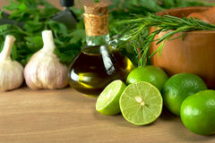 Limes and Other Seasoning. S such as rosemary, olive oil, garlic and parsley with mortar on wooden board (Selective Focus, Focus on the half lime and some of the Royalty Free Stock Images