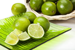 Limes on plate and in basket Stock Photography