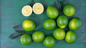 Limes on rustic dark green wood table Royalty Free Stock Photos
