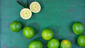 Limes on rustic dark green wood table Royalty Free Stock Images