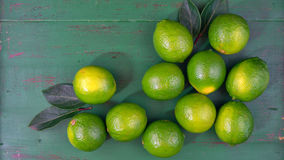Limes on rustic dark green wood table Royalty Free Stock Image