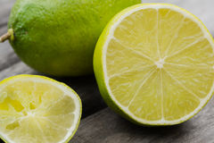 Limes. Sliced lime against a whole lime.  Squeezed lime in the corner Royalty Free Stock Photo
