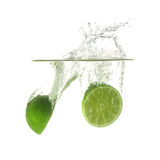 Limes splash on water, isolated on white background. Royalty Free Stock Photos