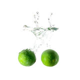 Limes splash on water on white background Royalty Free Stock Images