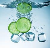 Limes splashing into water Royalty Free Stock Photos