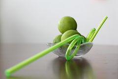 Limes in a fluted bowl with a straw Royalty Free Stock Image