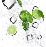 Limes with water splash and ice cubes Stock Photo