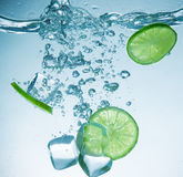 Limes with water splash and ice cubes Stock Images